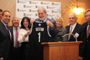 A Brooklyn Nets shirt is presented to keynote speaker John Sexton, president of New York University. - Brooklyn Archive
