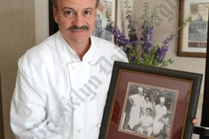 Pasquino Vitiello poses with a picture of his father Anthony Vitiello, who started Queen Restaurant, back in 1958. - Brooklyn Archive