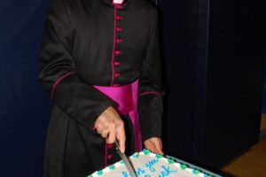 Msgr. Gigantiello cuts the cake. - Brooklyn Archive